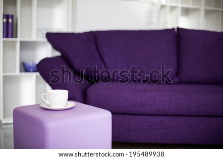 white cup in front of a purple couch