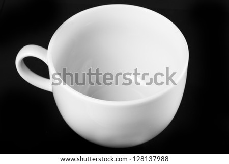 White cup isolated on black background. Black and white photo. - stock photo