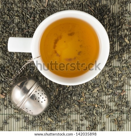 White cup of black tea on scattered tea over bamboo mat - stock photo