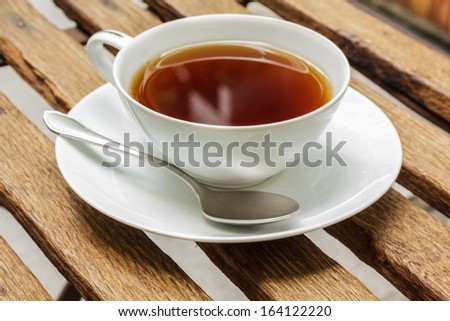 White cup of black tea on wooden battens. - stock photo
