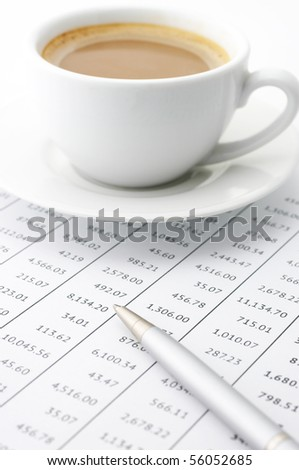 White cup of cappuccino and silver pen on paper table numbers.