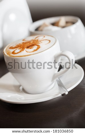 White cup of cappuccino stands on dark wooden table - stock photo