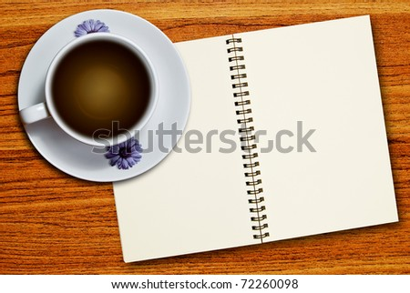 White cup of coffee and blank page notebook on wood table background