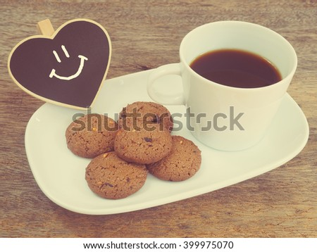 White cup of coffee and cookies.Good morning or Have a nice day concept.vintage filter effect