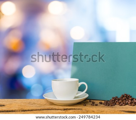 White cup of coffee and green chalkboard menu on wooden bar with  blurred light bokeh for background usage.