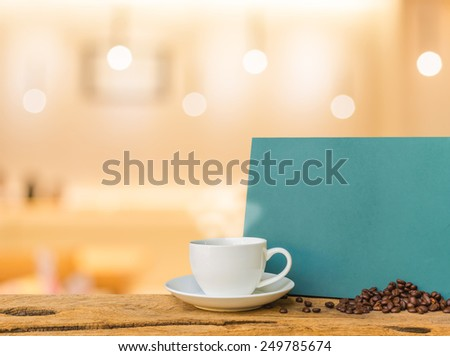 White cup of coffee and green chalkboard menu on wooden bar with Coffee shop blur background with bokeh image .  - stock photo