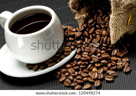 White cup of coffee and spilled coffee beans - stock photo