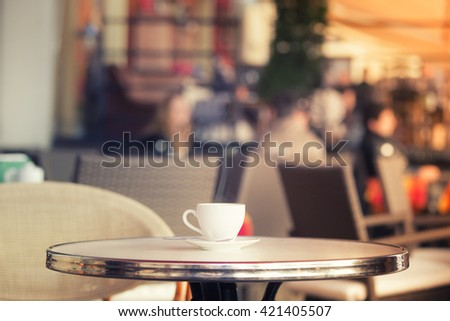 White cup of coffee at the summer cafe table