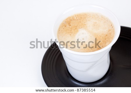 White cup of coffee on a black plate on a white background