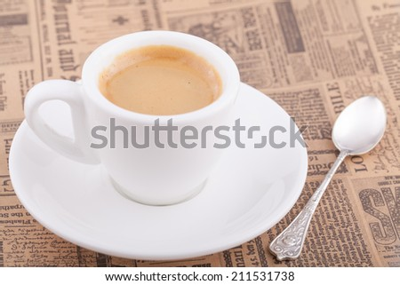 White cup of coffee on newspaper - stock photo