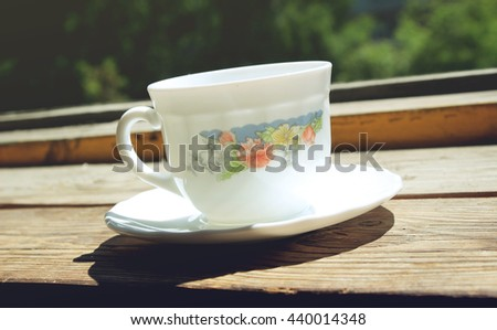 White cup of coffee on old wooden windowsill - stock photo
