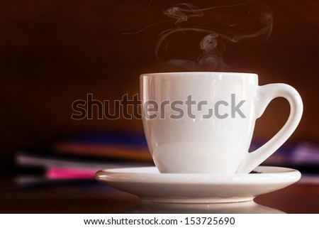 White cup of coffee on wooden background - stock photo