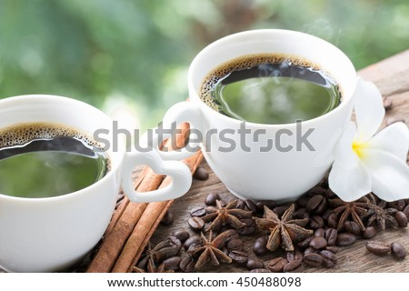 White cup of coffee on wooden, Flower, coffee beans, cinnamon sticks, star anise, Green tree background with heart shaped - stock photo