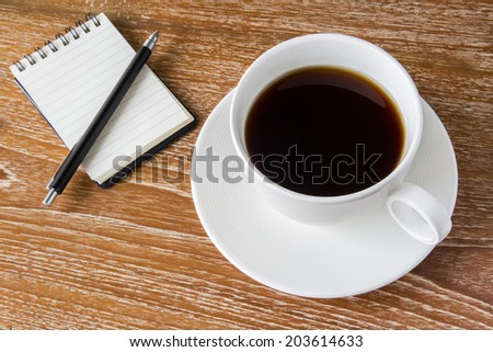 White cup of coffee on wooden table with notebook