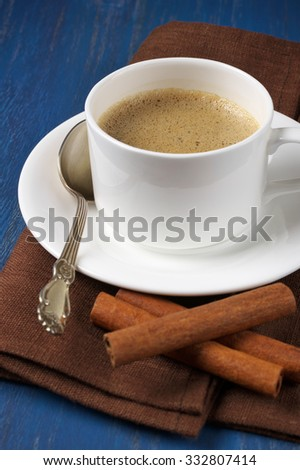 White cup of coffee with cinnamon sticks and brown napkin on blue wooden table.