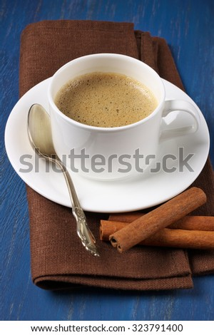White cup of coffee with cinnamon sticks and brown napkin on blue wooden table. Shallow DOF, focus on coffee. - stock photo