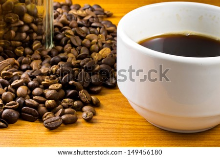 White cup of coffee with coffee beans - stock photo