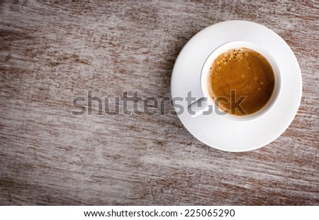 white cup of coffee with foam on saucer on old wooden surface with place for your text, top view - stock photo