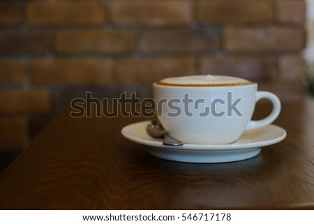 white cup of coffee with foam on the table and brick background