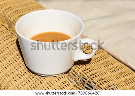 White cup of coffee with milk on wicker chair.