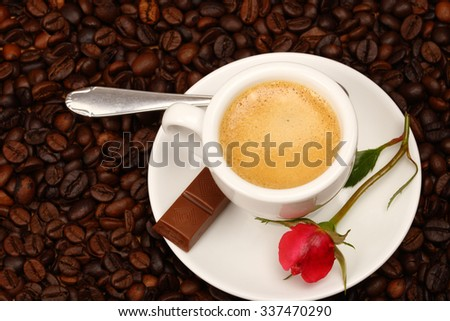 White cup of coffee with red rose - stock photo