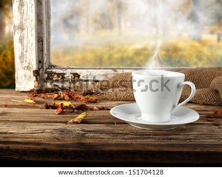 white cup of coffee with smoke and window  - stock photo