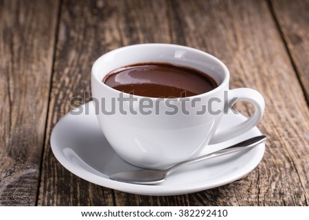 White cup of delicious hot chocolate on wooden table. - stock photo