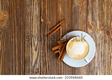 White Cup of hot Cappuccino and Cinnamon on brown wooden table. Top view. - stock photo