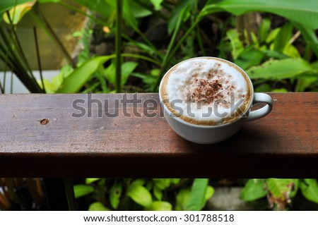 white cup of hot coffee on natural green background - stock photo