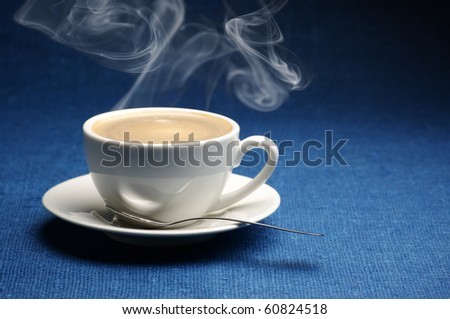 White cup of hot coffee with steam on dark blue canvas. - stock photo