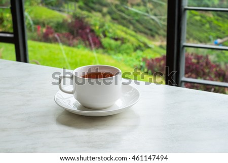 White cup of tea on white marble table in tea shop at Cameron Highlands, Malaysia.