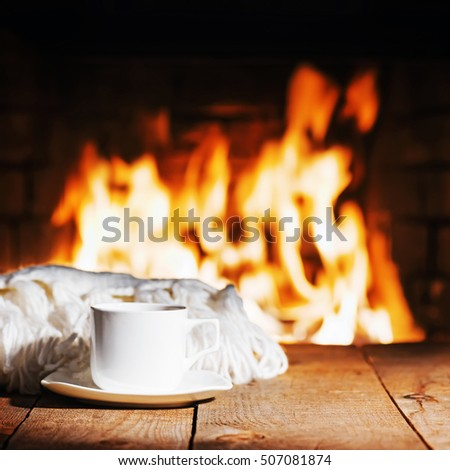White cup of tea or coffee and woolen scarf near fireplace on wooden table. Winter and Christmas holiday concept.