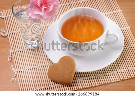 White cup of tea with a heart shaped biscuit and a flower - stock photo
