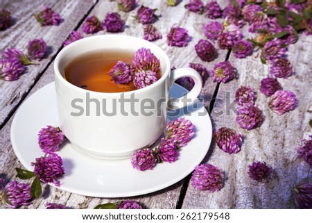 White cup of tea with  clover on old wooden table. - stock photo