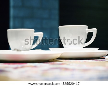 white cup on a black background. focus on the right cup