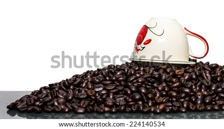 White cup on saucer upside down in a heap of roasted coffee beans. - stock photo