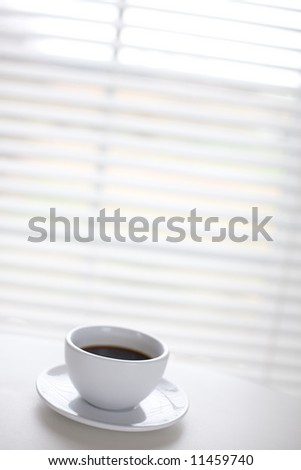 White cup on the table in front of window / copyspace - stock photo