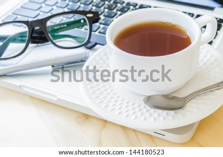 white cup tea&laptop on the wood table