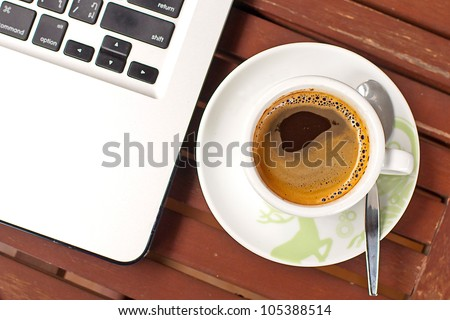 White cup with black coffee at business workplace