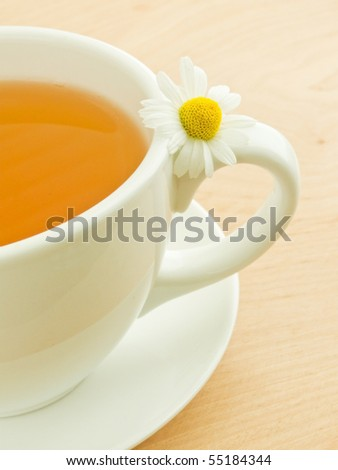 White cup with camomile tea and blossom. Shallow dof.