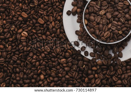 White cup with coffee beans. Coffee in beans macro. Abstract background texture.Coffee beans texture. Food background of coffee beans