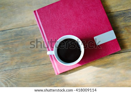 White Cup with coffee on a book in a red cover, wooden background, top view. - stock photo