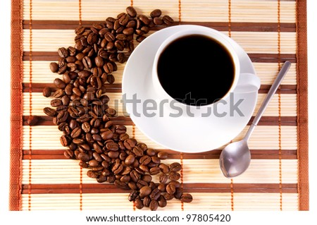 White cup with coffee on bamboo mat and coffee beans - stock photo
