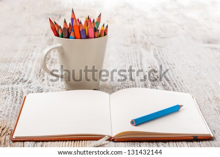 White cup with colorful pencils and notebook - stock photo