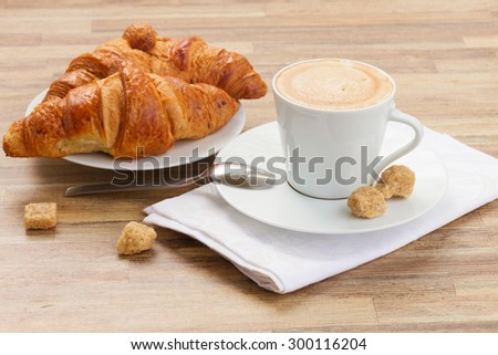 white cup with fresh espresso  coffee with water and croissant