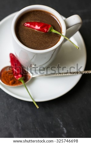 White cup with hot chocolate and spicy red chilli pepper