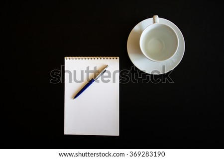 white cup with note on black background