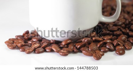 white cup with roasted coffee beans on clean simple background
