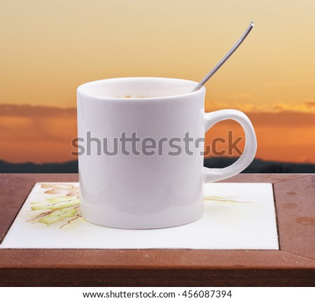 White cup with spoon with dawn light on the background, horizontal image - stock photo
