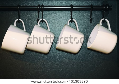 White cups hanging on wall. - stock photo